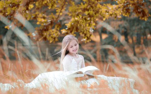 Обои Светловолосая девочка в белом платье читает книгу, сидя под деревом