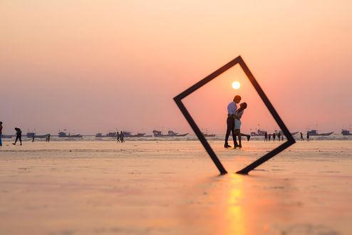 Обои Влюбленная парочка в рамочке и люди, гуляющие по побережью, фотограф Sanket Khuntale