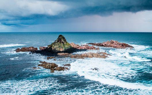 Обои Маленький каменистый островок в море, на который набегают волны, над морем нависают дождевые тучи