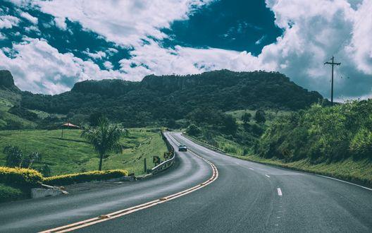 Обои Машина едет по извилистой асфальтовой дороге по направлению к холмам в пасмурную погоду, фотограф Kaique Rocha