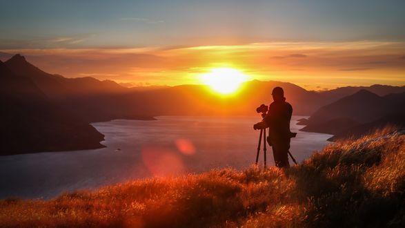 Обои Фотограф с камерой стоит на пригорке у реки