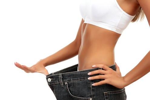 Обои Девушка оттягивает рукой джинсы, показывая на сколько она похудела
