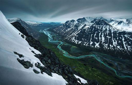 Обои Замерзшая река, протекающая вдоль заснеженных гор
