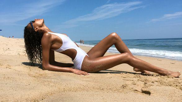 Обои Девушка в белом купальнике лежит на песке