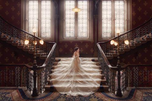 Обои Азиатка в свадебном платье с длинной юбкой, стоит на лестнице в холле богатого особняка