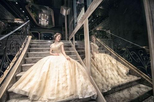 Обои Азиатка в бальном платье с пышной юбкой, стоит на лестнице отеля с большими зеркалами