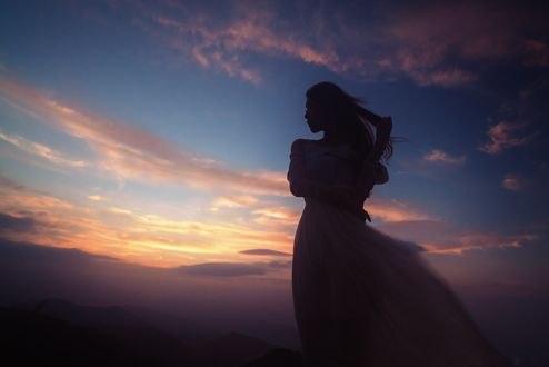 Обои Девушка в длинном платье стоит на фоне облачного неба