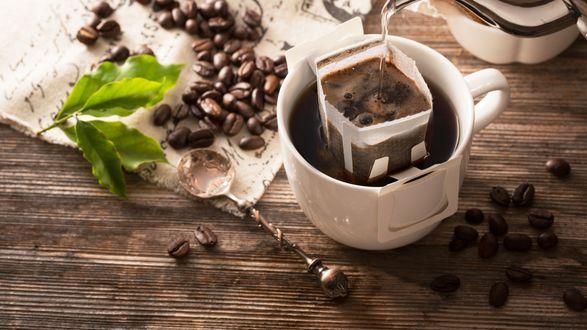 Обои Кофе заваривается в кофейной чашке, рядом листики и рассыпанные кофейные зерна