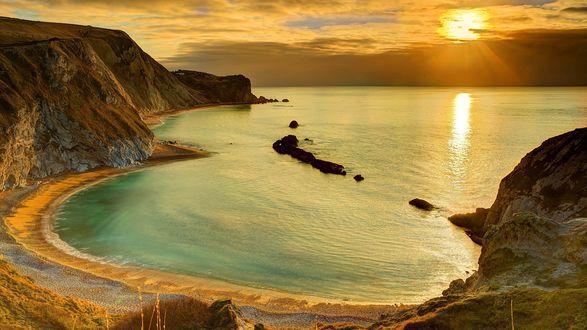 Обои Гладкое море в скалистой бухте на фоне тропического рассвета
