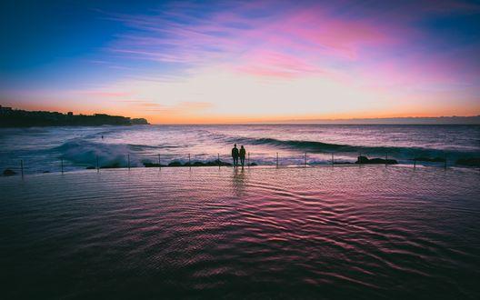 Обои Влюбленная пара стоит в набегающей морской волне на фоне заката