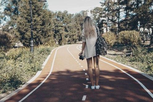 Обои Девушка стоит спиной на дороге с фотоаппаратом