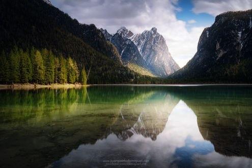 Обои Горы и лес под облачным небом и их отражение в озере, фотограф Juan Pablo de Miguel