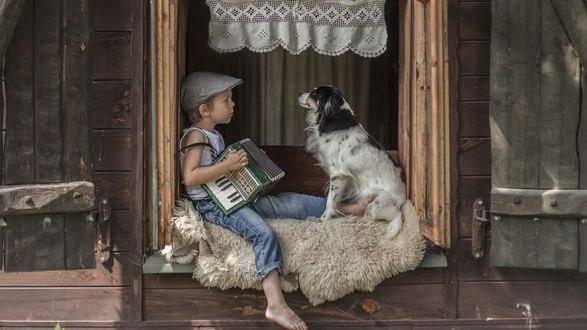 Обои Мальчик с аккордеоном сидит рядом с собакой на подоконнике