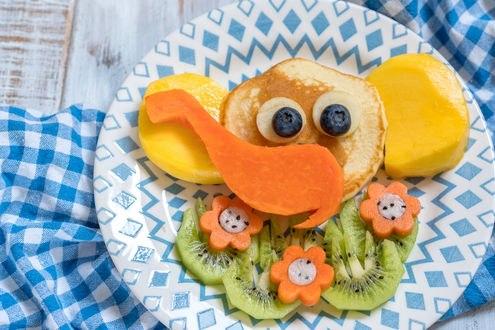 Обои На тарелке композиция из стопки блинов с фруктами и ягодами в виде смешного слоненка на поле с ромашками