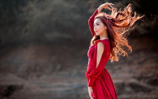 Обои Азиатка в красном платье с развевающимися волосами стоит на размытом сером фоне