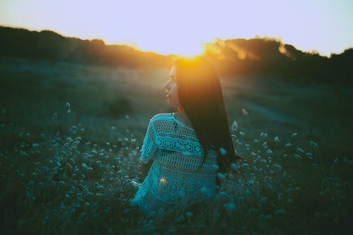 Обои Девушка стоит в поле на фоне заката