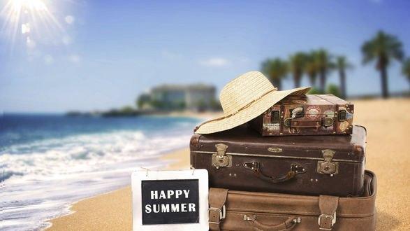 Обои Стопка чемоданов на берегу моря, сверху лежит шляпа, рядом табличка Happy summer / Счастливого лета