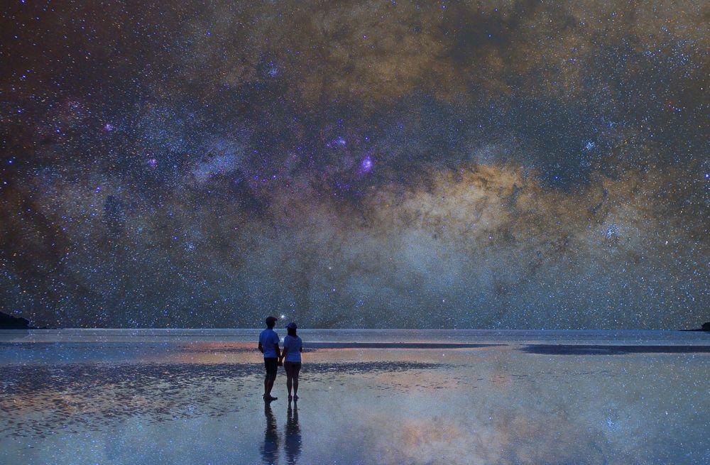 Обои для рабочего стола Парень и девушка стоят на берегу моря на фоне ночного неба и млечного пути