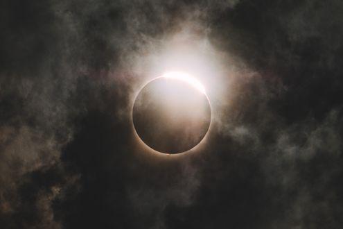 Обои Солнечное затмение в разрывах затянутого тучами неба