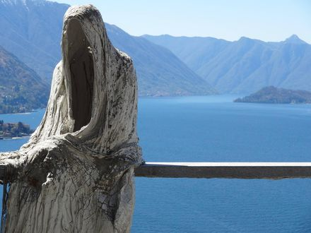 Обои Мрачная статуя фигуры в капюшоне сидит на фоне озера Комо и гор в тумане, Italy / Италия