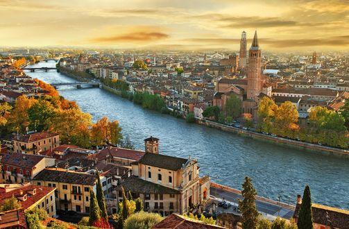 Обои Город со шпилями с высоты птичьего полета разделенный рекой осенью, на закате