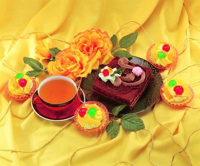 Обои Шоколадное пирожное на тарелке, маленькие кексы, чашка чая и желтые розы на желтой шелковой ткани
