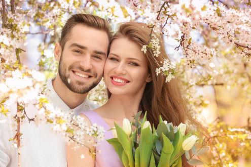 Обои Счастливая влюбленная пара среди весенних веток вишни и с белыми тюльпанами в руках у девушки
