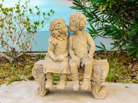 Обои Скульптуры ангелов целуются на лавочке в парке летом на фоне голубого неба и листьев