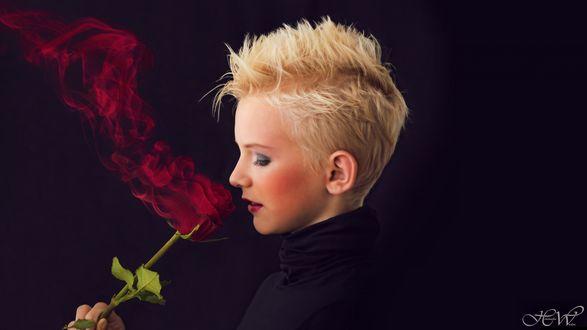 Обои Девушка блондинка нюхает красную розу с красным дымом