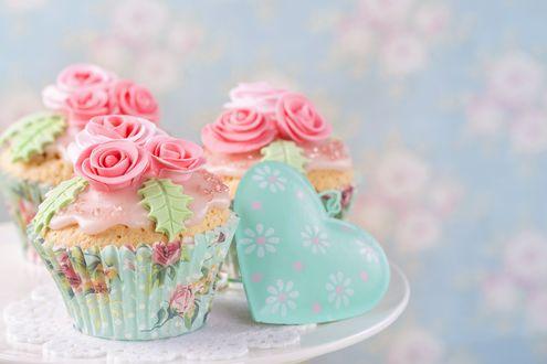 Обои Кексы с кремовыми розочками и фигурка сердечка на белой тарелке на размытом пастельном фоне