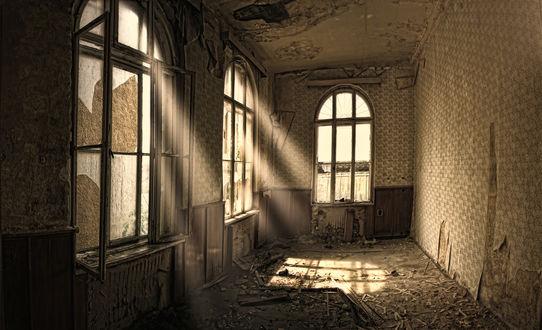 Обои Разрушенное помещение с оборванными обоями и выбитыми стеклами, через которые пробивается дневной свет