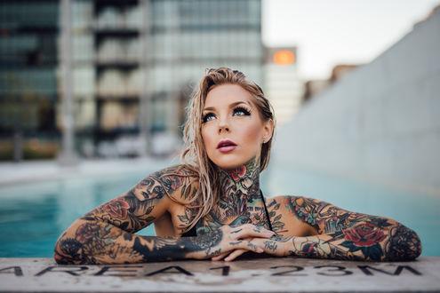 Обои Девушка с мокрыми волосами в бассейне в татуировках на размытом фоне города