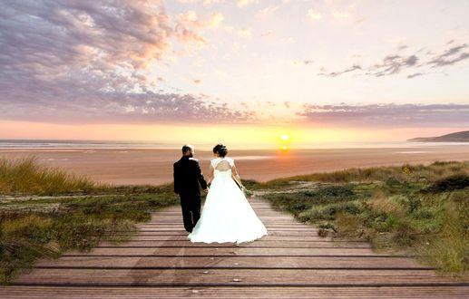 Обои Жених с невестой, идущие по мостику к морю, на восходе солнца