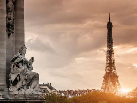 Обои Эйфелева башня в Париже и каменная скульптура на закате на фоне вечернего неба