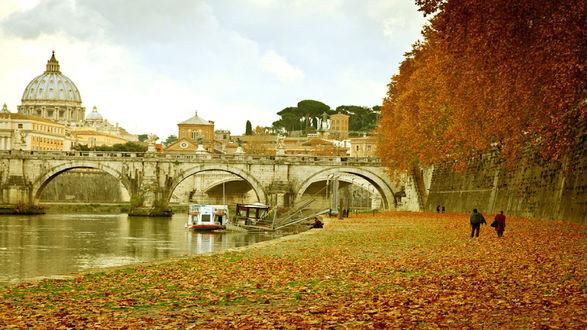 Обои Rome, Italy / Рим, Италия) осенью. Берег реки с мостом, усыпанный желтыми листьями с деревьев, по реке плывет корабль, на берегу гуляют люди, вдалеке виден Собор Святого Петра