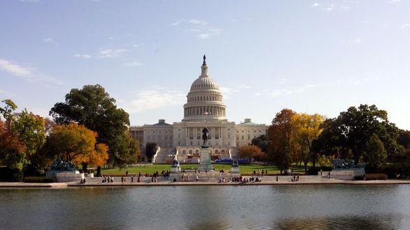 Обои Капитолий в Вашингтоне у реки осенью среди желтых деревьев. Люди гуляют на берегу
