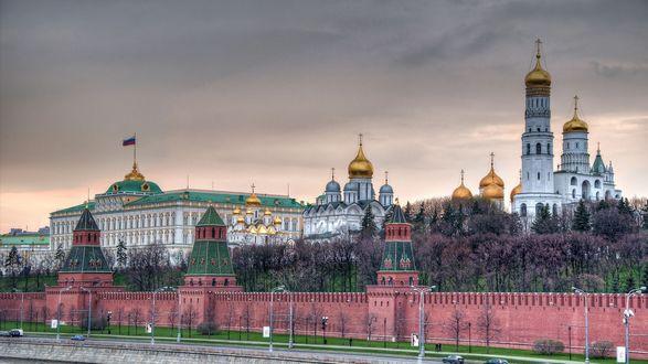 Обои Кремлевская набережная Москвы реки, дворец с флагом и золотые купола Храма Христа Спасителя под ванильным небом