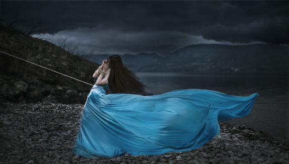 Обои Девушка в развевающемся голубом платье, со связанными руками стоит на фоне мрачного неба, фотограф Lichon