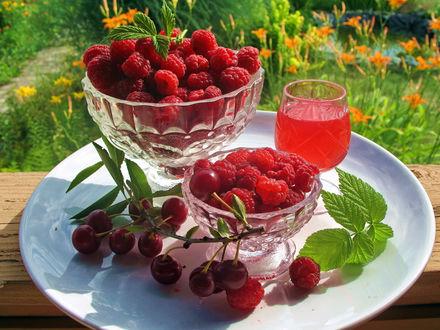 Обои Сок, малина в вазочках и вишня с листочками на белом блюде на фоне размытого сада