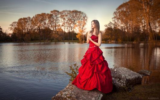 Обои Девушка в длинном красном платье стоит на камнях у озера с осенними деревьями, фотограф Lods Franck