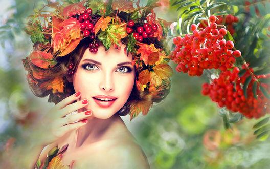 Обои Красивая девушка в веночке из осенних листьев и ягод стоит возле веточки рябины