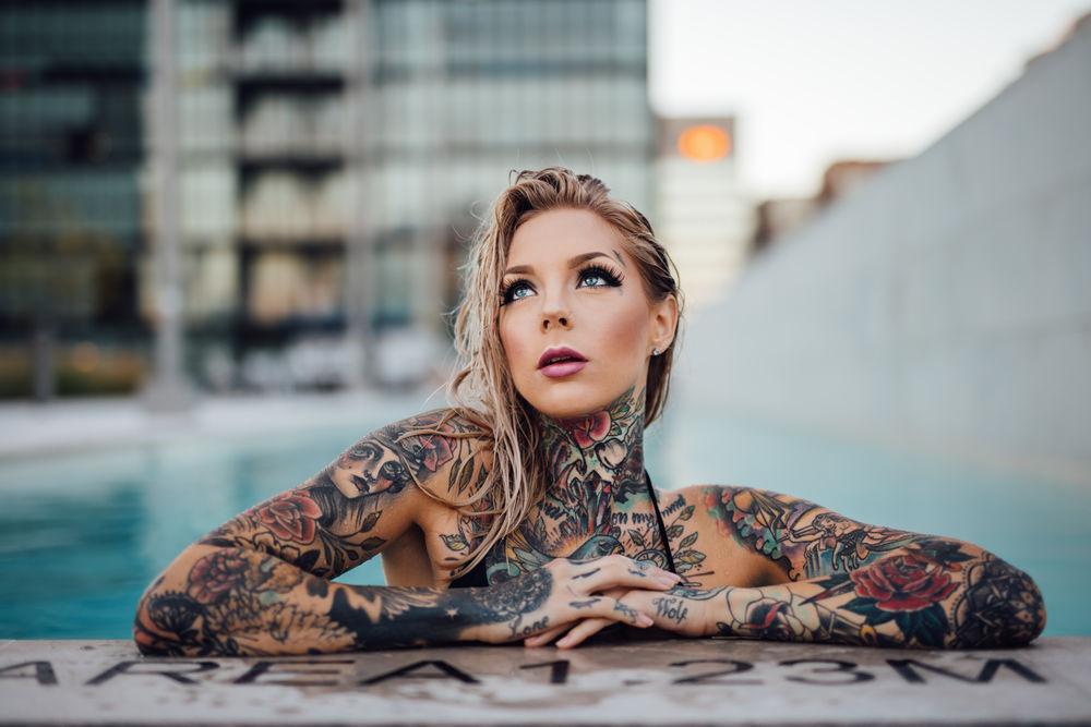 Обои для рабочего стола Девушка с мокрыми волосами в бассейне в татуировках на размытом фоне города