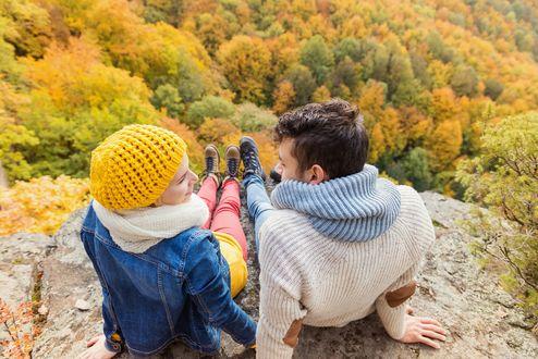 Обои Осенний лес, вид с горы на которой седят парень с девушкой
