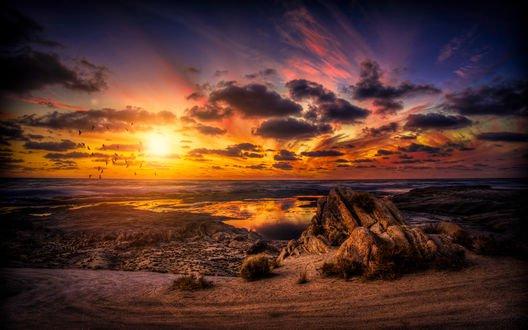 Обои Заходящее солнце опускается в тучи над высохшим озером