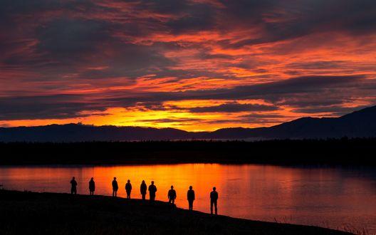 Обои Люди стоят на берегу озера, залитого светом солнца, заходящего за линией гор