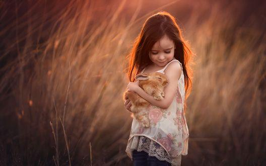 Обои Девочка Миа с маленьким кроликом на руках стоит на фоне сухой травы, фотограф Lisa Holloway