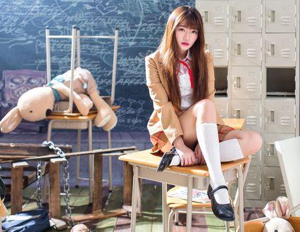 Обои Японская школьница сидит на стуле в классе среди беспорядка