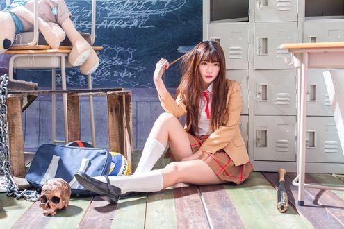 Обои Японская школьница сидит на полу в классе среди беспорядка: бейсбольной биты, черепа, плюшевого зайца