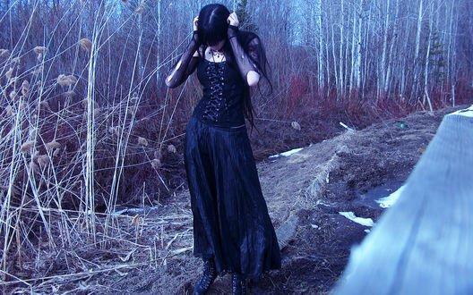 Обои Девушка в черном платье стоит на обочине дороги зимой
