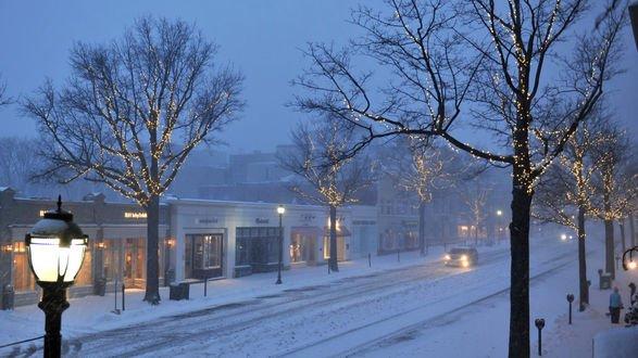 Обои Улица в городе зимой в Рождество. Деревья наряжены гирляндами. люди идут по улице вечером
